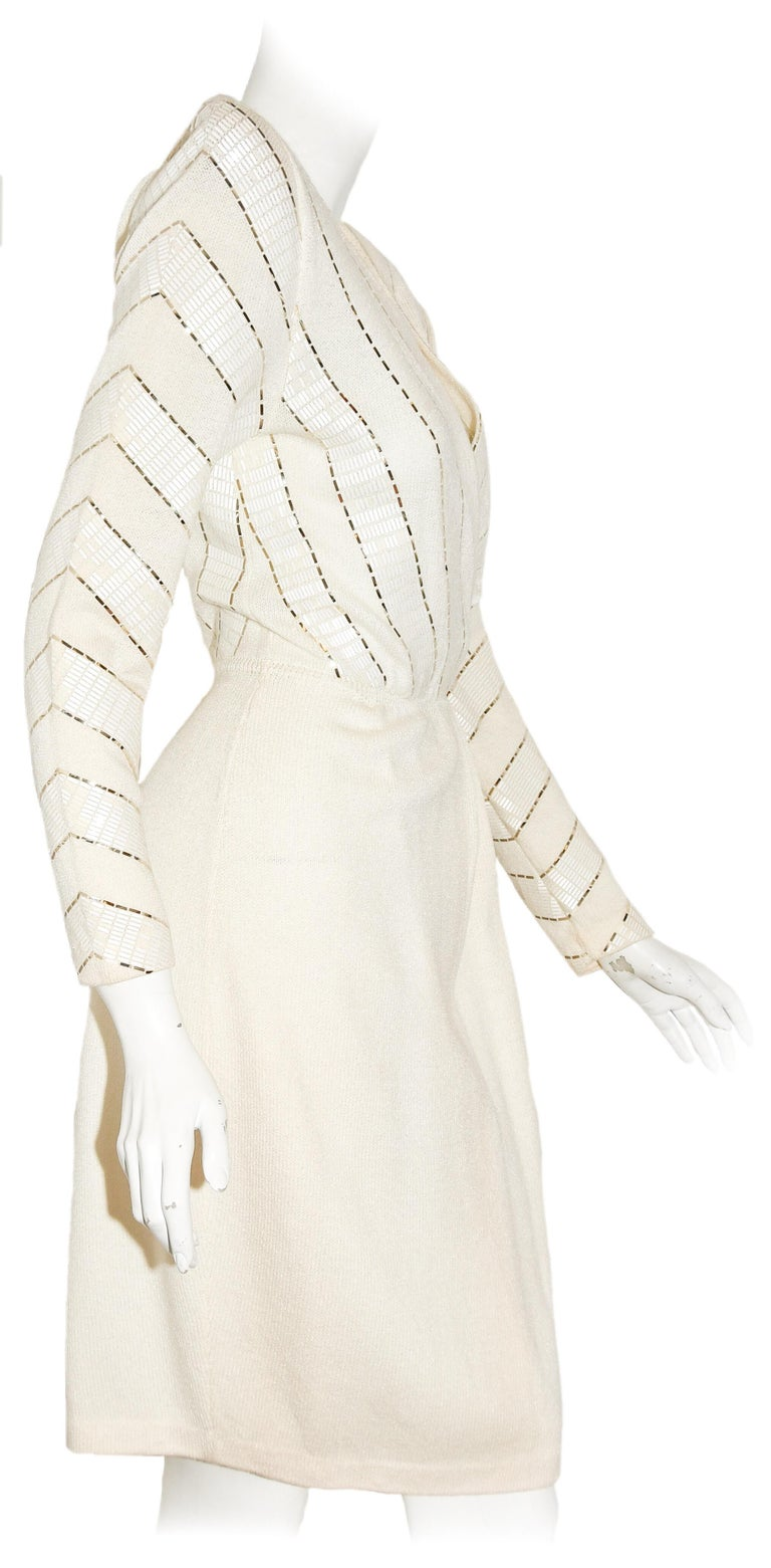 St. John winter white V neck, 3/4 sleeve dress is highlighted with gold tone sequins in a asymmetric pattern at the bodice and sleeves.  This  knit dress is pleated from the waist and includes an opening, at front, down to the knees.  Dress is