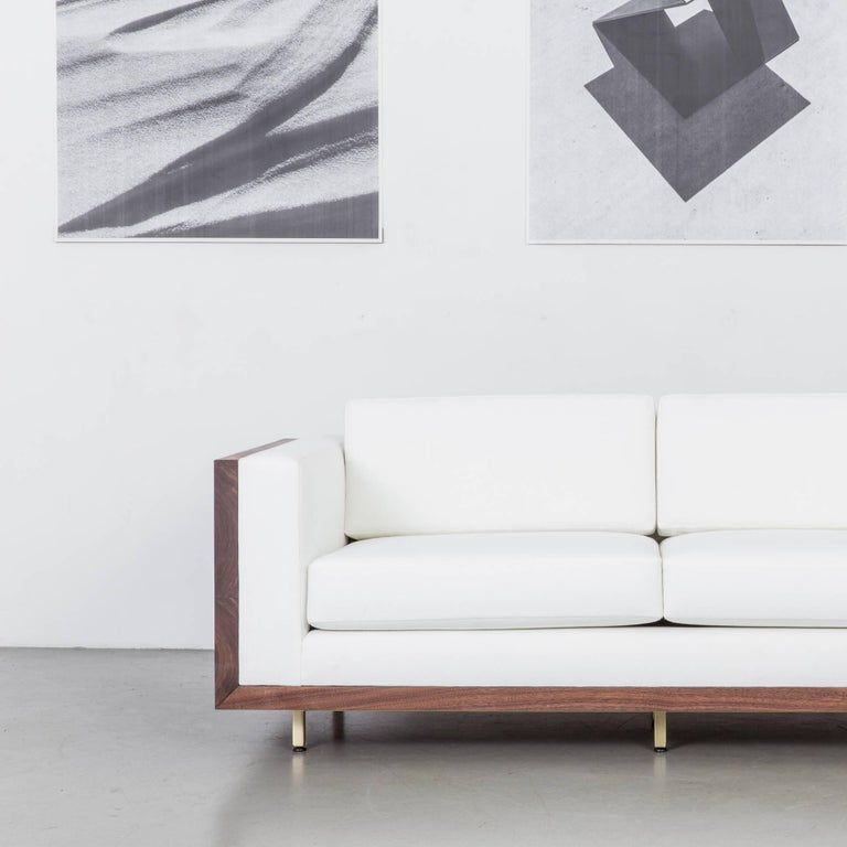 The St. Pierre Sofa showcases our commitment to expert craftsmanship and timeless design. A single claro walnut slab frame featuring brass butterfly joints rests on an elegant brass base with a plush, inviting seat.   The sofa's minimal, modern