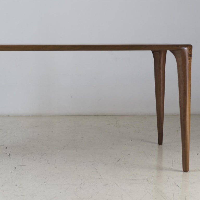Truly one of a kind, this table is part of the S collection, characterized by smooth surfaces, gentle curves and the elegant joints between the table's legs and top. Crafted in the best solid Italian blonde walnut on the market, the table is further