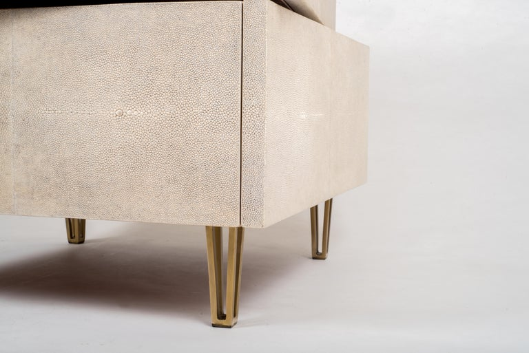 The irregular stacked bedside by R&Y Augousti is an elegant piece with its fun geometry. This bedside table is completely inlaid in cream shagreen and sits on discreet cut-out bronze-patina brass. This bedside table includes a total of three