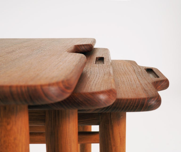 Stacking tables with tops in massive teak and legs in oak. Beautiful handle details. Designed by the Danish architect Kurt Östervig and produced by Jason, Ringsted, Denmark. Labelled with