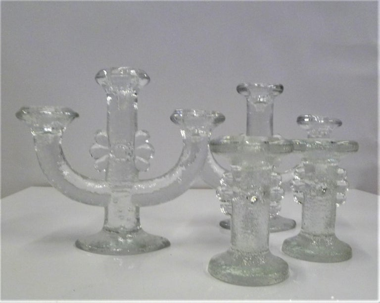 A grouping of 4 textured lead crystal glass candleholders from the 1970s by Swedish Designer Staffan Gellerstedt ( b. 1944) for Pukeberg Glassworks of Sweden. The set consists of heavily textured glass holders with an abstract flower motif, two