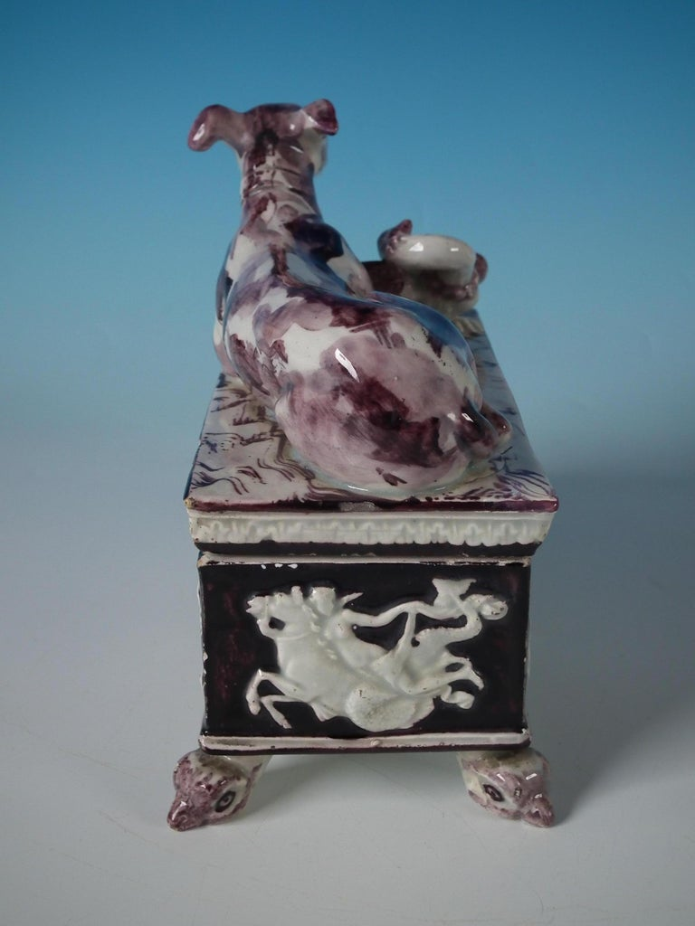 Staffordshire pottery Pearlware box and cover which features a recumbent greyhound and a bird to the cover. Pictorial scenes in relief to the sides of the box. The whole, stood on a footed base. Decorated 'in the round', decoration to front and