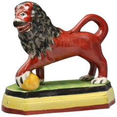 Staffordshire Pottery Figure of a Lion with Paw on Ball, Early 19th Century