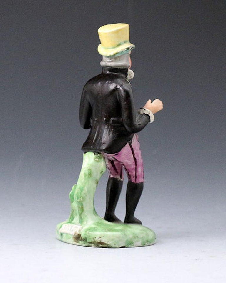 Dated: 1820 Staffordshire England  A fine Staffordshire pottery pearlware theatrical figure of Paul Pry with the title I HOPE I DON'T INTRUDE impressed in the base in black capitals.  This quality figure is well modelled standing on green
