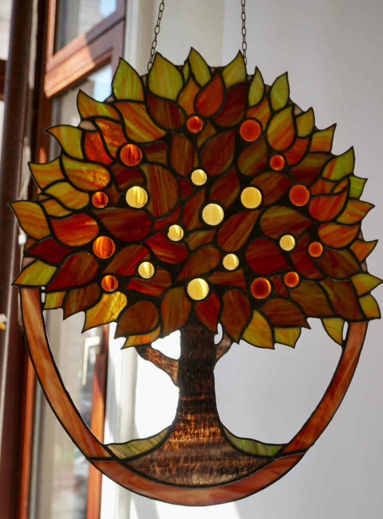 Offering this stunning stained glass panel on chain. In the shape of a floral tree with various colors and pattern. Also have many shades of green, red, yellow and orange. Measures: Height 45 cm. Width 39 cm.