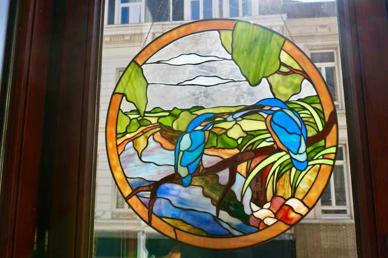 Offering this stunning stained glass panel on chain. Round in shape with various colors and pattern with two birds sitting in a tree. Also have many shades of green, red, blue, orange and white. Signed J.P. 1994. Measures: Diameter 45 cm.