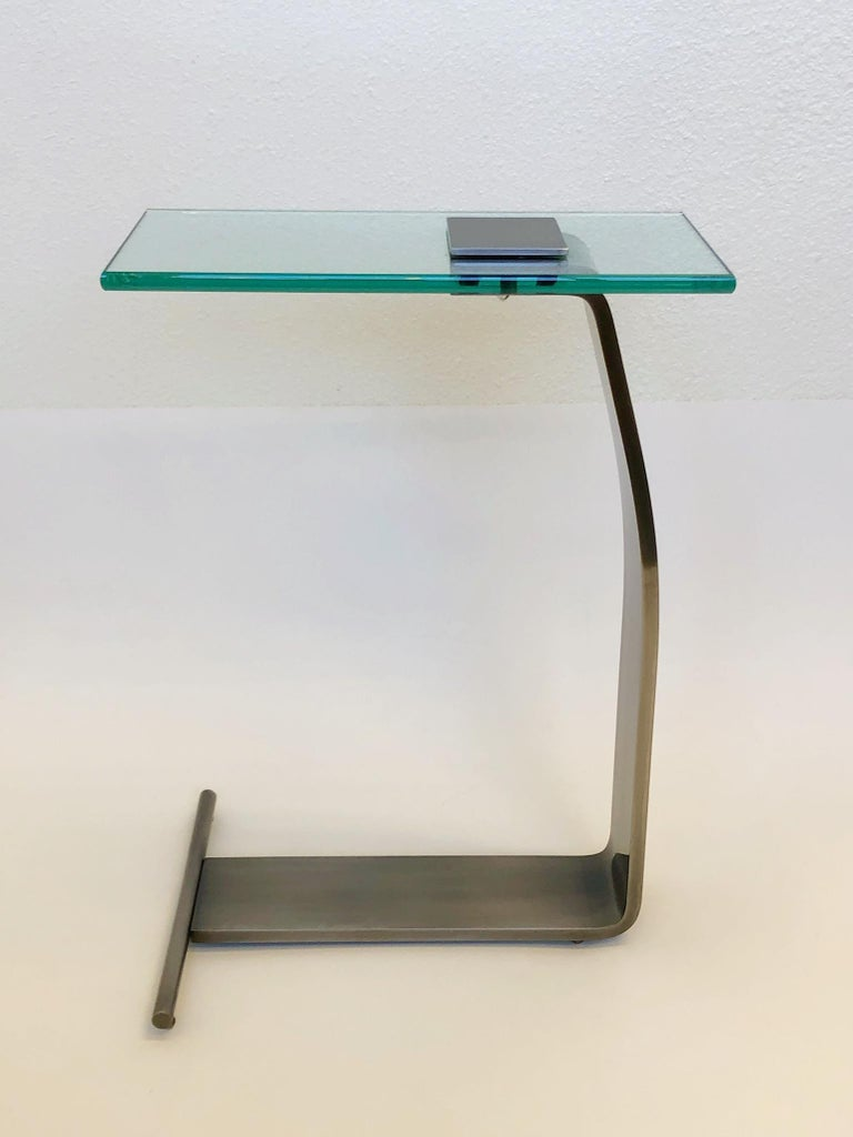 """A stainless steal and glass top occasional table design by Kaizo Oto for Design Institute of America in the 1980s Dimensions: 22"""" high, 16""""wide, 8"""" deep."""