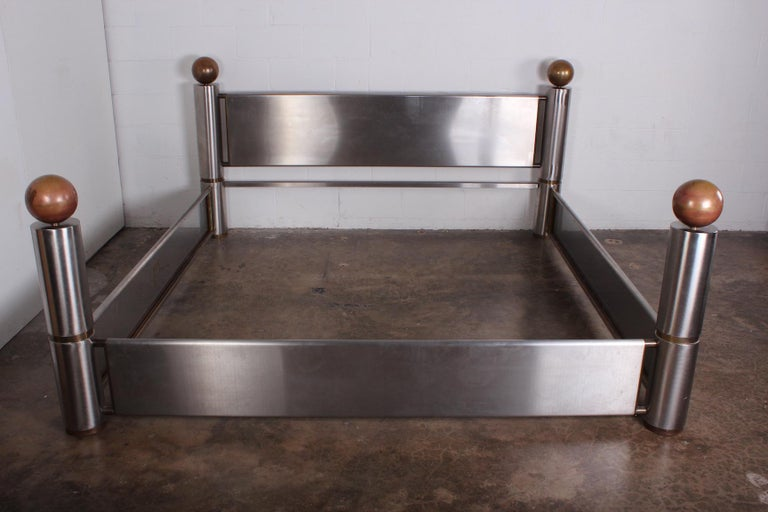 A finally crafted stainless steel and patinated brass king size bed, 1980s. Interior measurements: 81.5 x 83.75.