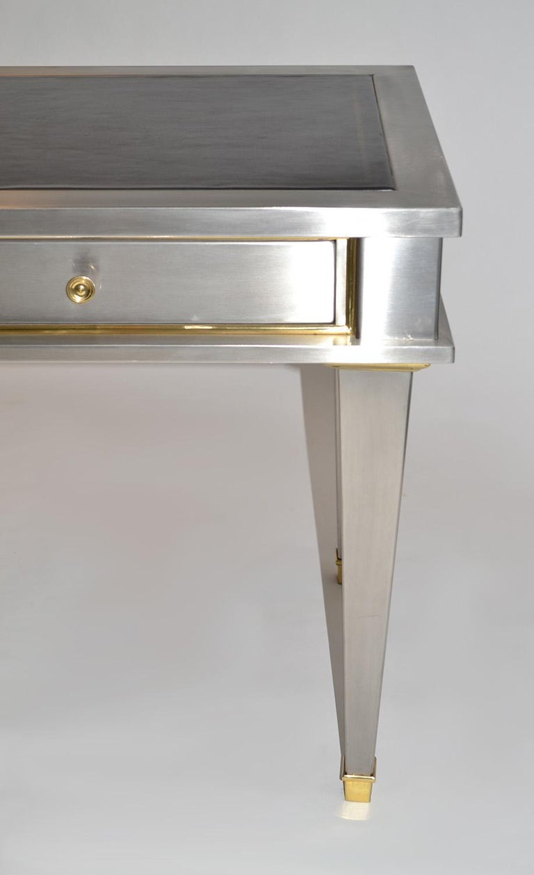 Stainlesssteel bronze neoclassical revival desk 20th century (mid-) after John Vesey. A diminutive steel writing table, desk or bureau plat after a design by John Vesey. Clad in brushed steel with gilt bronze accents and handles, the desk features