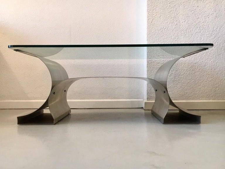 Brushed stainless steel base and clear glass top coffee table by François Monnet, produced by Kappa, France, circa 1970s.  Most of the furniture created by François Monnet feature entire steel sheets that are bent or curved, therefore, these pieces