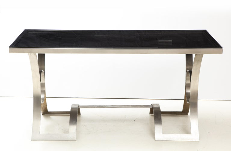 Rare stainless steel table from France, circa 1970.   Table consists of a highly distinctive, curvilinear base with a custom glass top in a smoked grey finish. The last three images picture the surface beneath the glass top, which consists of a