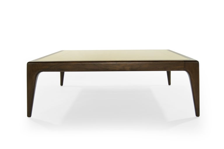 This modernist coffee table lets each material shine and play to its strength. Solid walnut is sculpted with organic curves and soft edges, so every connection looks seamless. The tabletop is inlaid with solid brass and decorated with linear seams.
