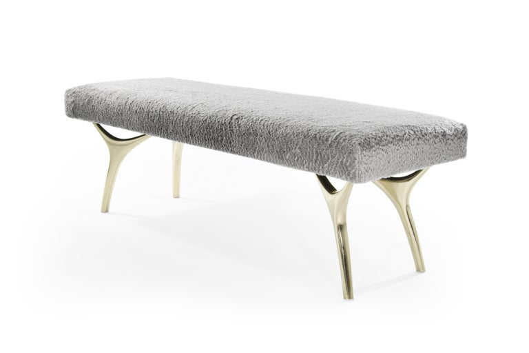 The Crescent Bench floats effortlessly, poised on brass fingertips. Inspired by 20th century visionaries like Vladimir Kagan and Gio Ponti, this bench offers a unique perspective. The plush bench cushion is fully wrapped in soft silver mohair
