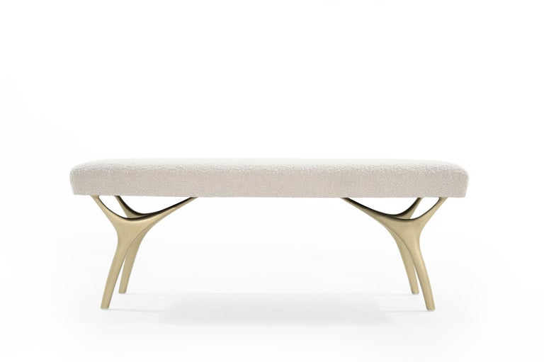 The Crescent Bench floats effortlessly, poised on brass fingertips. Inspired by 20th century visionaries like Vladimir Kagan and Gio Ponti, this bench offers a unique perspective. The plush bench cushion is fully wrapped in off-white soft bouclé