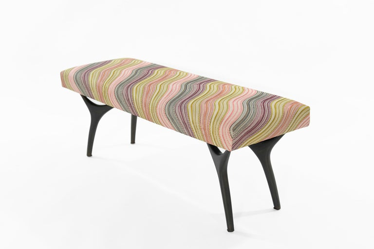The Crescent Bench floats effortlessly, poised on bronze finished brass fingertips. Inspired by 20th century visionaries like Vladimir Kagan and Gio Ponti, this bench offers a unique perspective. The plush bench cushion is fully wrapped colorful