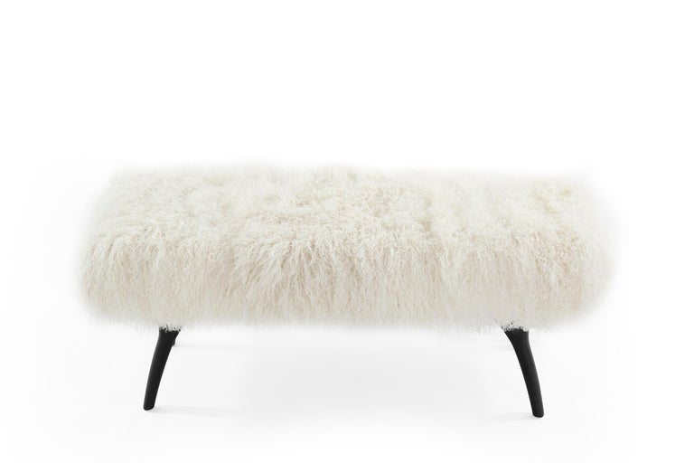 The Crescent Bench floats effortlessly, poised on bronze fingertips. Inspired by 20th century visionaries like Gio Ponti and Vladimir Kagan, this bench offers a unique perspective. The plush bench cushion shown upholstered in creamy Mongolian wool