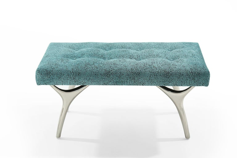 The Crescent Bench floats effortlessly, poised on nickel fingertips. Inspired by 20th century visionaries like Vladimir Kagan and Gio Ponti, this bench offers a unique perspective. The plush bench cushion shown upholstered in blue / green chenille