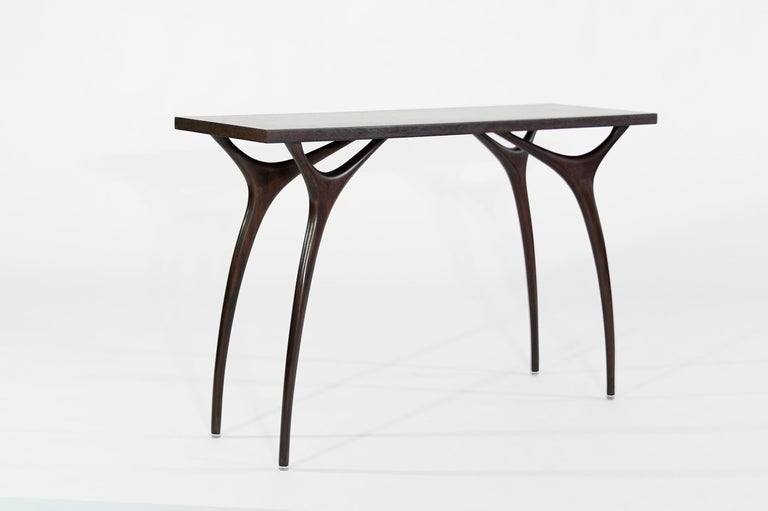 The Crescent Console Table is beautifully balanced and surprisingly strong. We were inspired by Giuseppe Scapinelli, a visionary of Brazilian furniture design. The narrow, spindly legs are sculpted out of solid mahogany and reach up from the earth