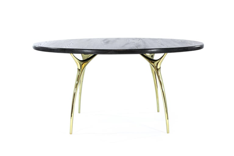 The Crescent Dining Table captures Gio Ponti's Italian design aesthetic with gleaming metal and fluid curves. Four polished brass legs feel surprisingly organic, like delicate stalks that split and expand into slim branches. This delicate base is
