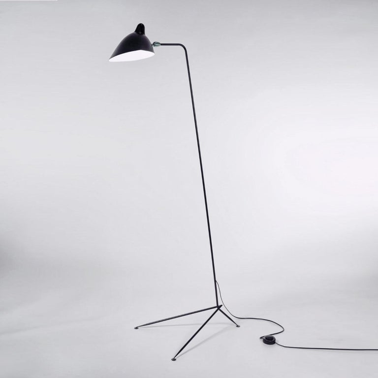Clean, simple lines describe the elegance of this Serge Mouille floor lamp. A long, slender arm, supported by a tapered triangular base, allows the swiveling shade to illuminate at any angle. With brass accents.  Available in black or white.