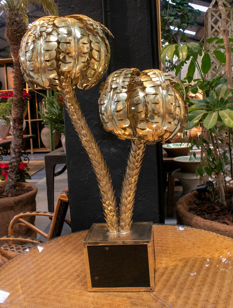 Standing polished golden brass twin palm lamp with a square base.