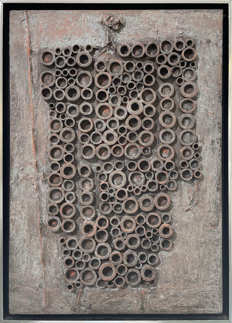 This Modern Abstract Expressionist painting by Stanley Bate is made with oil paint and 3-dimensional wooden shapes on canvas. The warm metal grey paint is highly textured, while the circular shapes are adhered in an organic shape with corners and