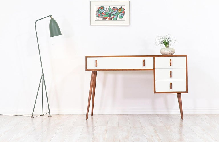 Stylish modern writing desk designed by Stanley Young for Glenn of California in the United States, circa 1950s. This striking design features a walnut wood frame sitting on angled tapered legs, with white lacquered front detailing and intricate