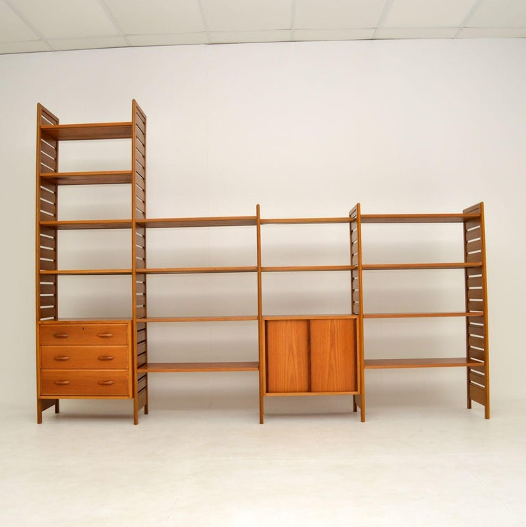 A large and impressive teak Ladderax shelving system by Staples. This was made in England and dates from the 1960's.  This four bay system consists of two tall ladder rails, three shorter ladder rails, a three drawer chest, a sliding door cabinet