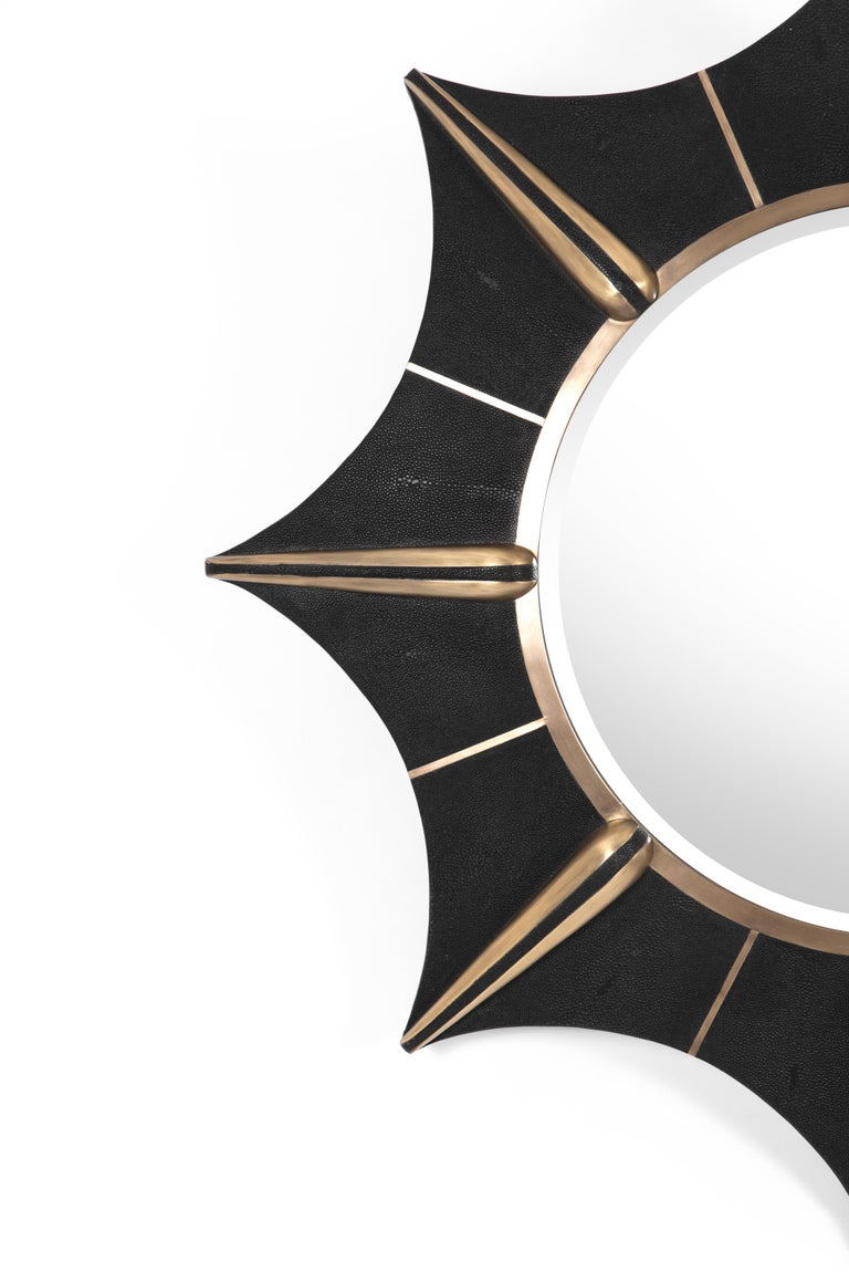 The star mirror in black shagreen and bronze-patina brass details is a celestial inspired piece that gives a dramatic statement to any room. This is the perfect accent piece to dress up any wall with elegance and fantasy.  The dimensions of this