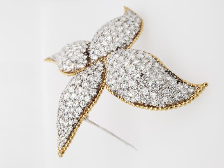 This one of a kind Brooch designed as a pinwheel is set with numerous round diamonds weighing approximately 34 Carats. Set within a Yellow Gold Frame. The stone Setting is impeccable, giving off enormous luster!   This 3 inch brooch will really make