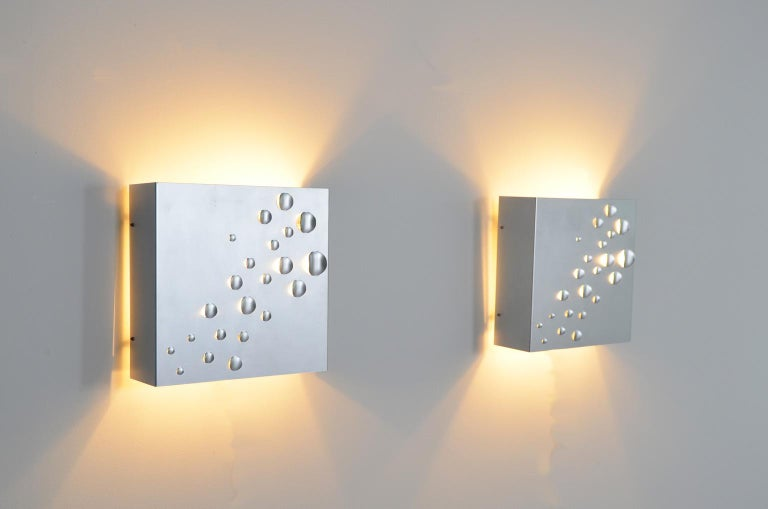 These 1960s metal wall sconces also known as model C1624 were designed by Jelle Jelles for RAAK, Amsterdam. The perforated metal brings a spectacular light effect. No wonder the name of the lamp is Star shower.