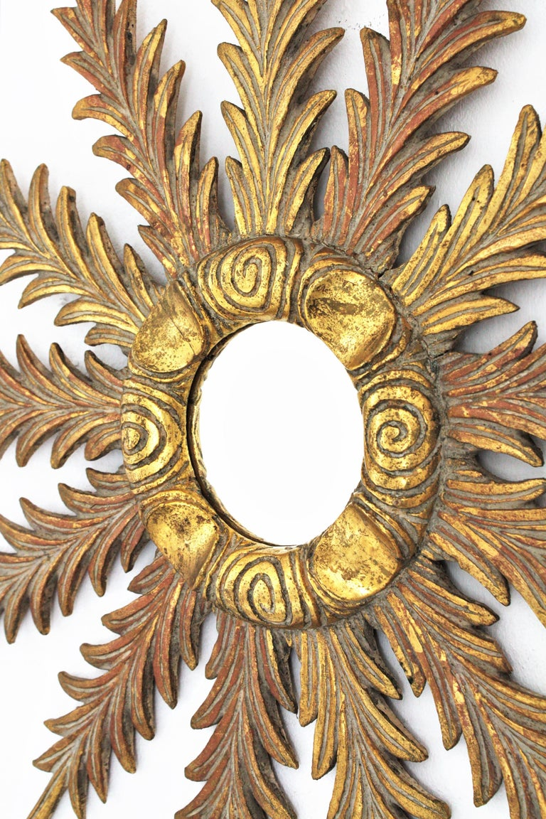 Elegant leafed starburst sunburst mirror in the style of Baroque, Spain, 1930s. Finely carved wood covered with gesso and 24-karat gold leaf finishing. Excellent vintage condition. Terrific aged original patina. Measures: 66 cm diameter // glass