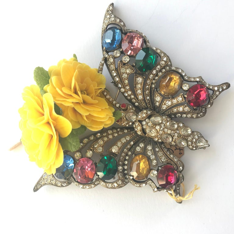 A wonderful rhinestone brooch in the shape of a butterfly. The whole brooch is set with 10 large cut, colorful rhinestones. The rest of the body is completely covered with small to large clear rhinestones. A typical work from the 1930/40s work USA,