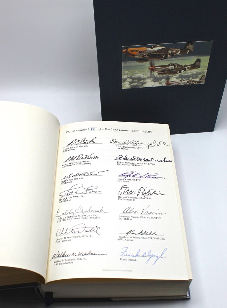 Olynyk, Frank. Stars & Bars: A Tribute to the American Fighter Ace 1920-1973. London: Grub Street, 1995. Deluxe Limited edition signed by author and 13 Fighter Aces. Original dust jacket. Presented in custom slipcase.  This deluxe limited edition