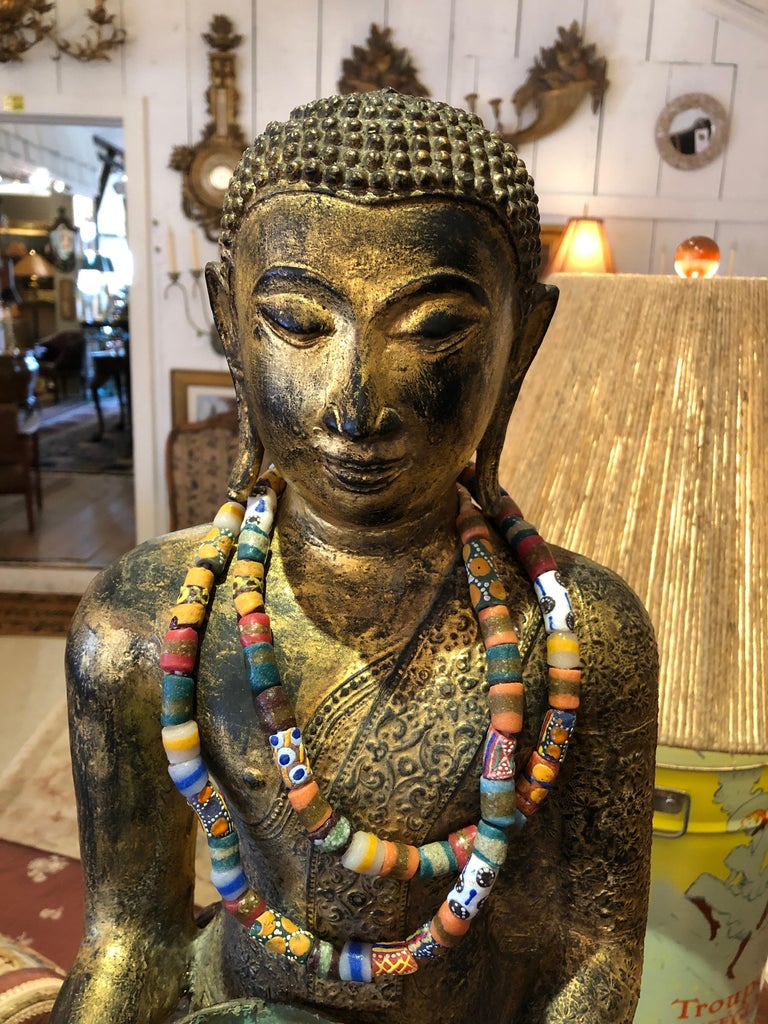 An especially beautiful Thai bronze Buddha having meticulous detail on the head and robe, with lovely gestural hands that hold a turquoise patina cup. A turquoise bracelet adorns the statue's wrist and multicolored tribal necklaces are a rich touch.