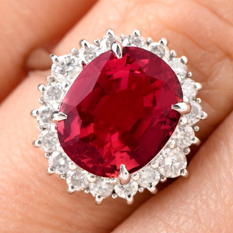 This Diamond and Pink Tourmaline ring comes with the versatility  of being worn as an engagement ring of color or a stately cocktail ring and was crafted in Platinum. Adorning the center is an oval shaped deep and rich colored Pink Tourmaline