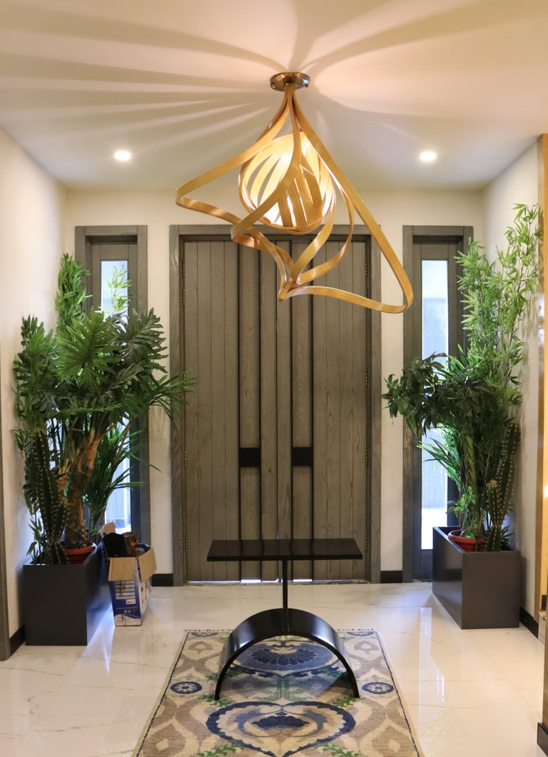 A chandelier made in solid ashwood using wood bending techniques. A single light is placed in a wooden cocoon which releases light with linear gaps creating a distinct lighting ambiance. This is further layered with bentwood designs surrounding the