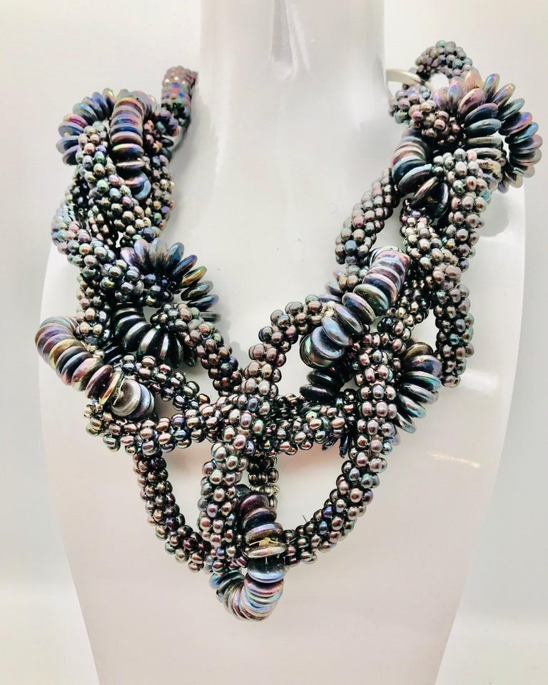Black Pearl necklace shown is made of number of circular loops joined and composed into a necklace. It was a very labor intensive design because the  tiny 1/8' dark fresh water round pearls made into loops and held together by 1/4