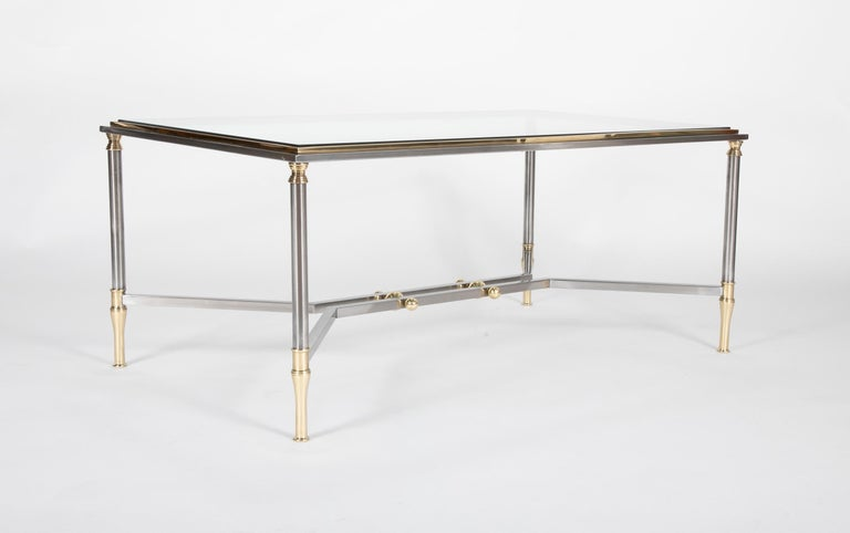 A Maison Jansen style coffee table in steel and brass with glass top.