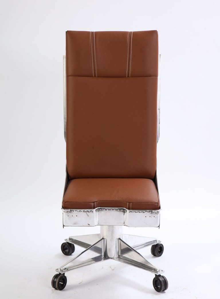 A modern high-back swivel chair featuring a polished, industrial-style pierced and riveted steel frame and tan leather upholstered seat with contrasting white stitching. The seat is raised on a four-point polished steel base with centreless casters.