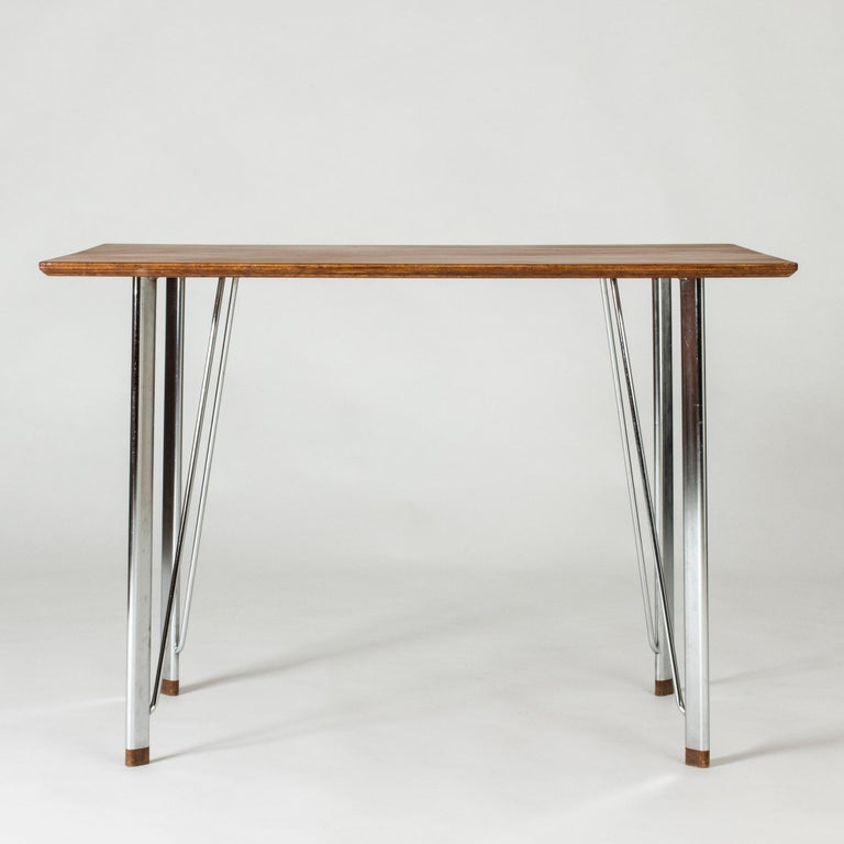 Elegant, minimalist desk by Arne Jacobsen. Sleek steel frame with wooden feet, beautiful teak table top. Neat size.