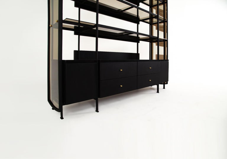 The Collector's cabinet is constructed in blackened steel combined with a blackened oak cabinet fitted to its interior. The cabinet is weighed down with black marble and is intersected by the cabinets' frame. One-way reflective bronze glass hugs the