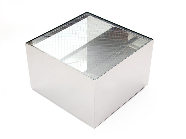 A stainless steel cube-form table designed by Joe d'Urso. Table rests on recessed casters with a safety glass top. Produced by Knoll in the USA, circa 1970s.