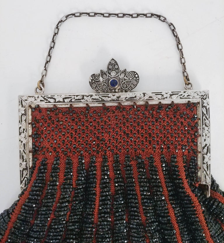 1920s Steel Cut Red Crochet Purse with Filigree Detail. Intricate Art Nouveau clasp and hardware with decorative blue stone. Fully lined with inner side pocket.