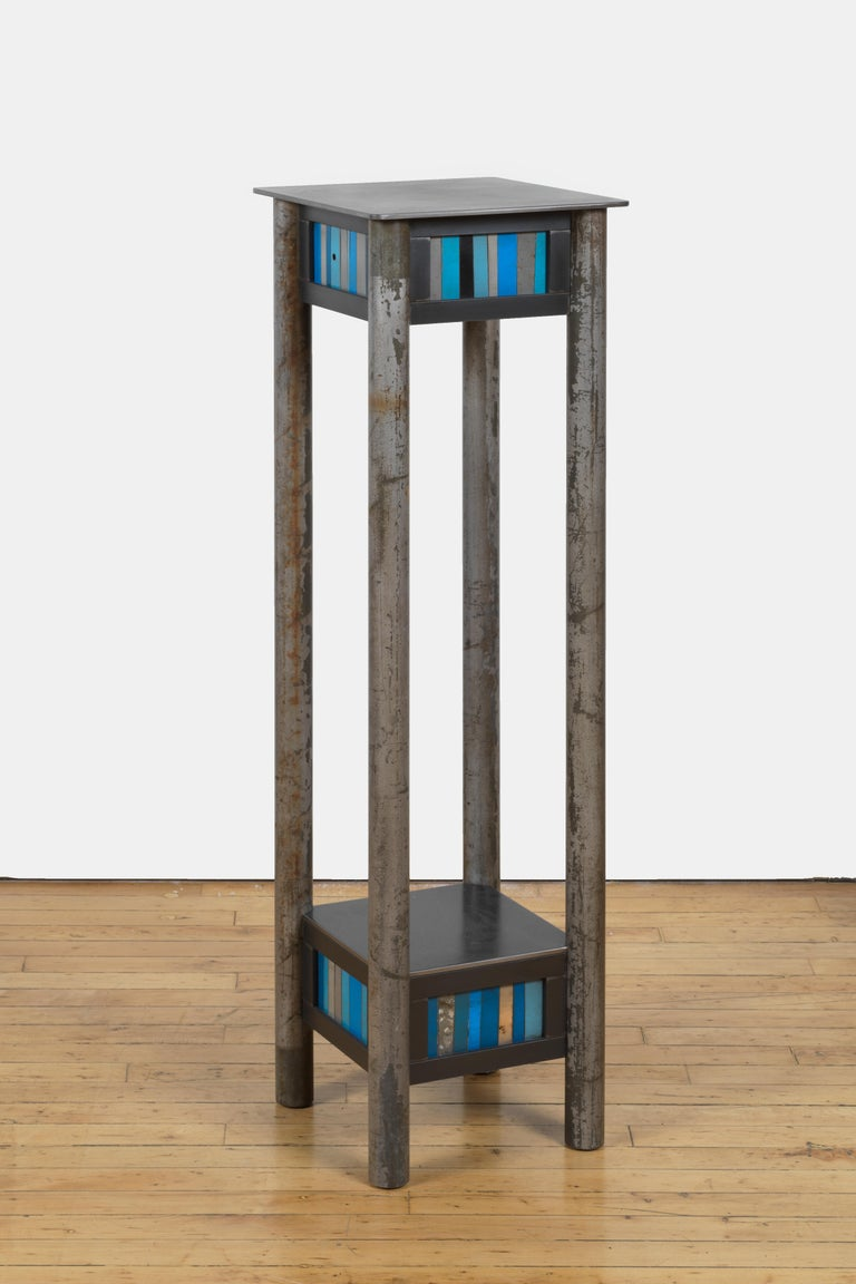 This is a welded steel pedestal with a low shelf and a quilted skirt of found metal strips arranged in a quilt pattern inspired by the quilts of Gee's Bend Alabama. Each piece of furniture is unique and made by Jim Rose. The skirt contains a mix of