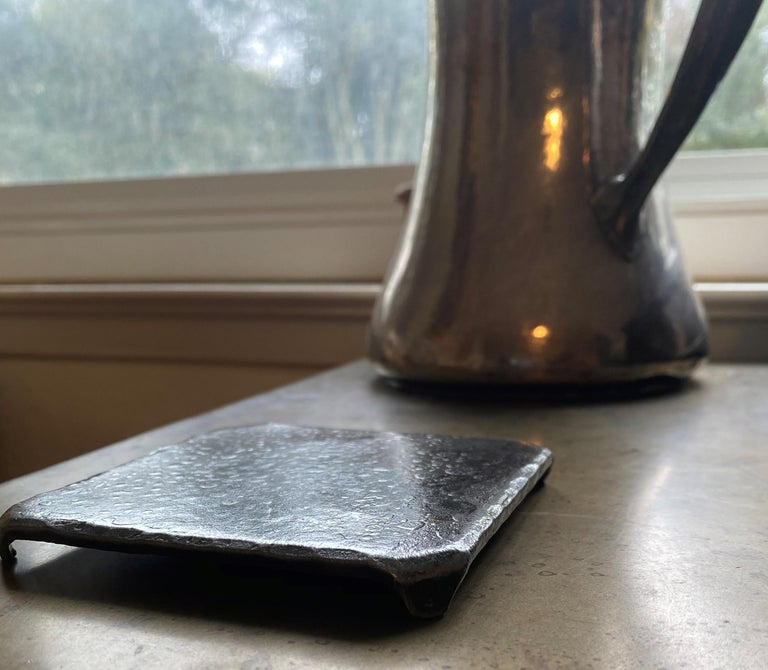 A handcrafted, steel square coaster with hammered, beveled edges. Wire brushed and sanded to accentuate the forged details. A glossy clear coat enhances the richness of the finish and texture. Forged over the anvil's edge to create the feet it