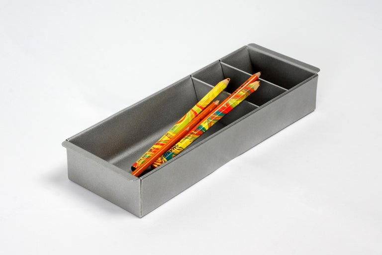 Once the insert to a classic tanker desk's utility drawer, we repurposed this neat Industrial piece for use as a desktop organizer. Steel has been newly powder-coated in metallic Bengal silver. Features three slots, ideal for storing coins, pens and