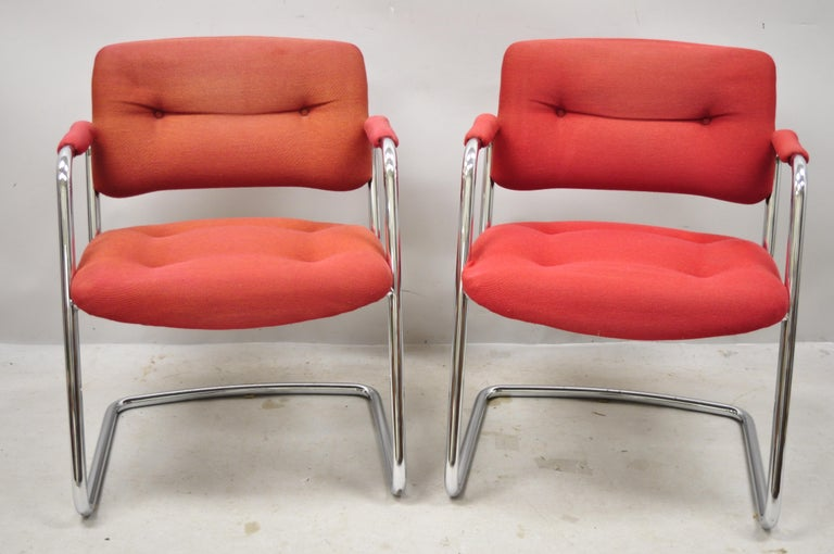 Steelcase Mid-Century Modern tubular chrome red upholstered arm lounge chairs (B). Item features sleek tubular chrome frames, red tufted upholstery, upholstered armrests, original label, very nice vintage item, clean modernist lines, quality