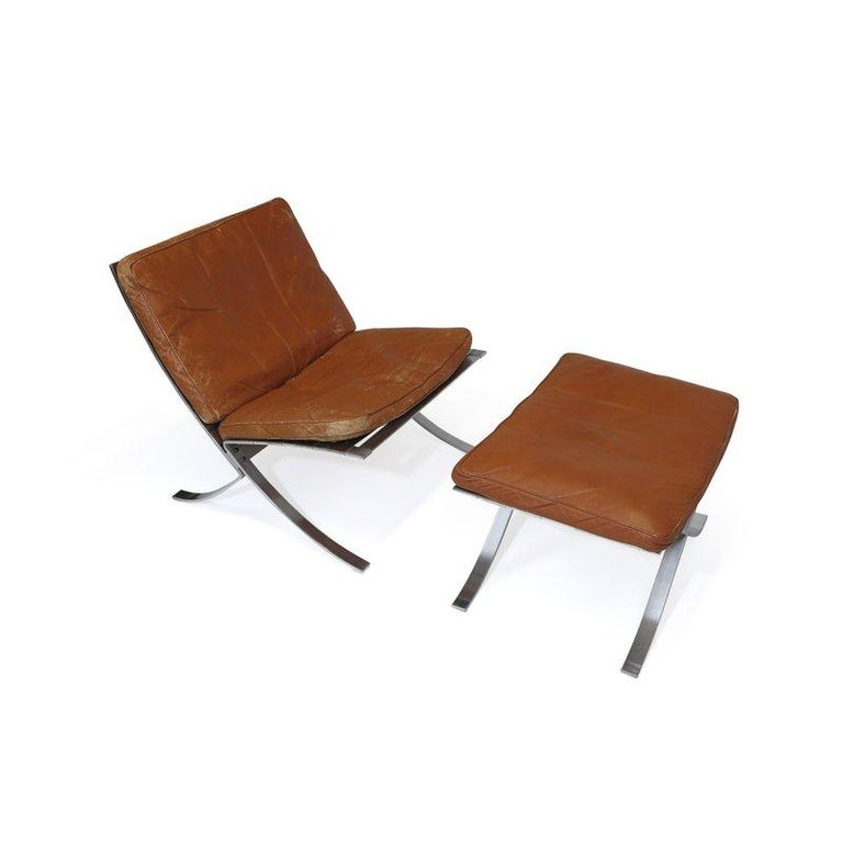 Steen Ostergaard steel frame lounge chair with original patinated leather cushions filled with down and rare foot stool.